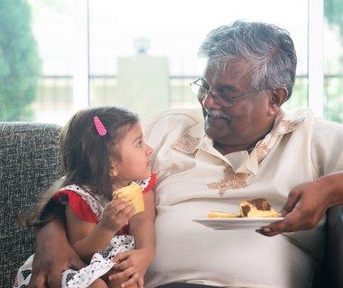 Grandparent and grandchild eating cake