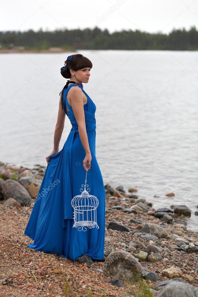 girl in a blue dress with an empty bird cage