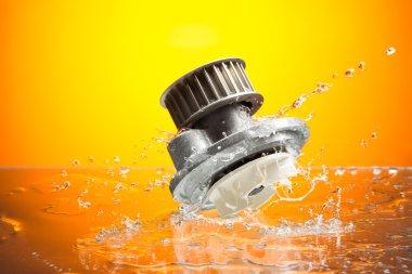 Auto parts, engine cooling pump in water splash on orange backgr