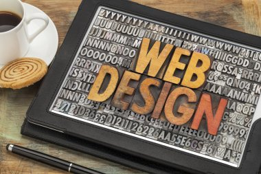 Web design in vintage wood and metal letterpress type on digital tablet with a cup of coffee and cookie stock vector