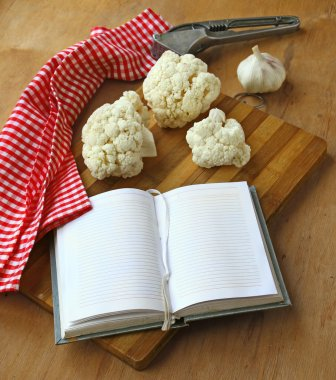 Open notebook with cauliflower and garlic