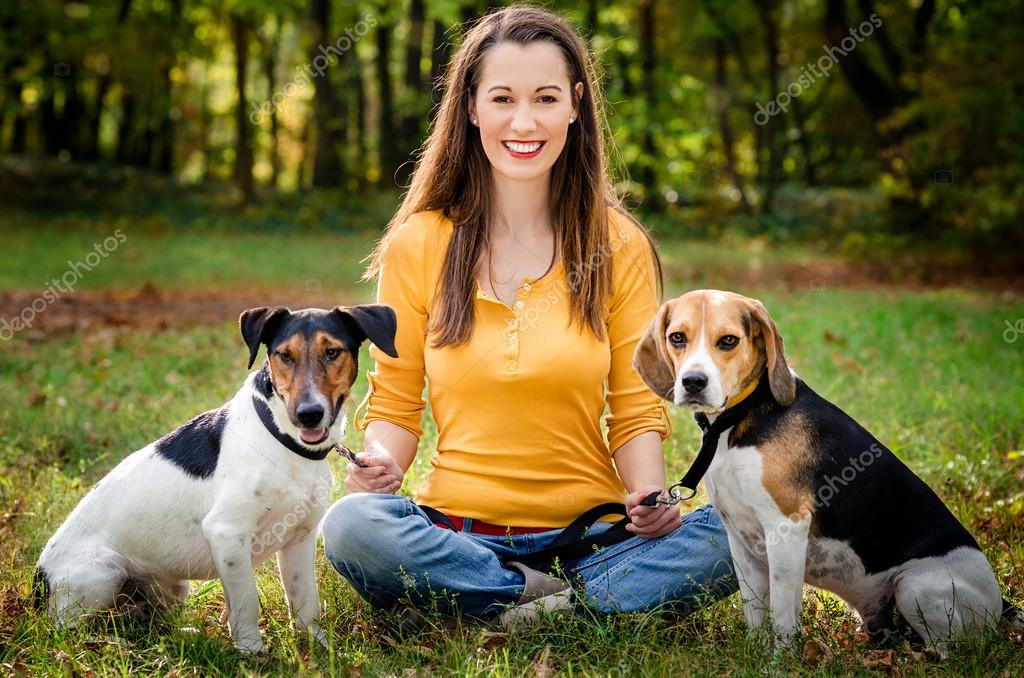 A beautiful woman and his dogs posing outside