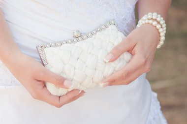 Bride holding white handbag close-up