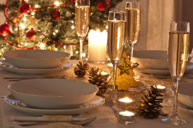 A decorated christmas dining table with champagne glasses