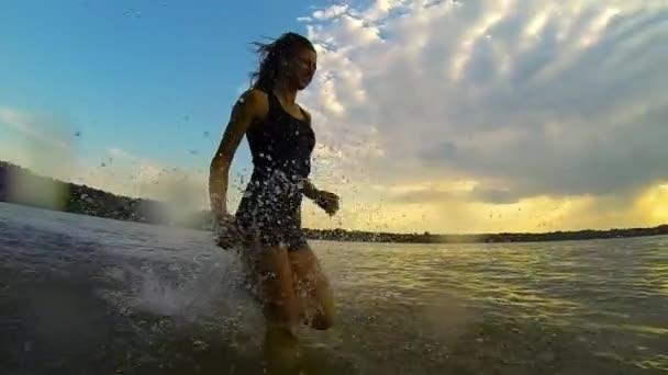 žena běží ve vodě v pomalém pohybu - letní sport