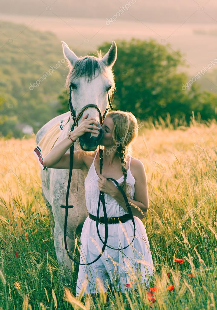 Blonde long hair woman kissing beautiful horse