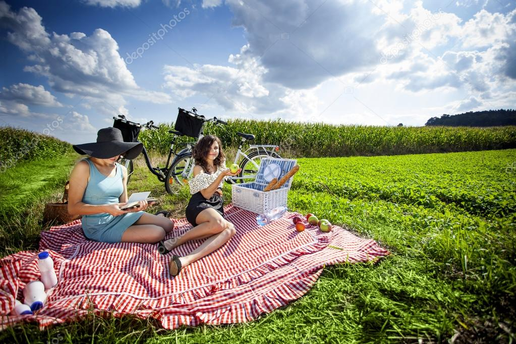 Two pretty girls ejnoy the sun in picnic