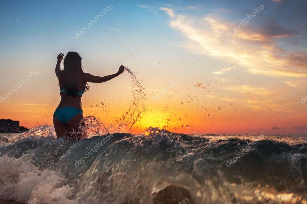 Happy woman running in the sunset on the beach