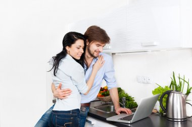 Couple using laptop at their kitchen