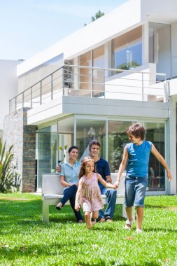 Family in front of big modern house