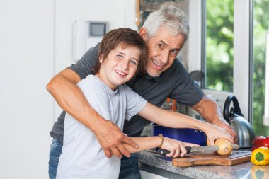 Grandfather and little boy cooking