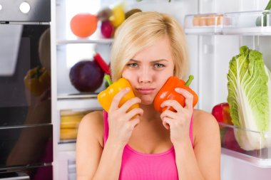 Girl hold red and yellow peppers