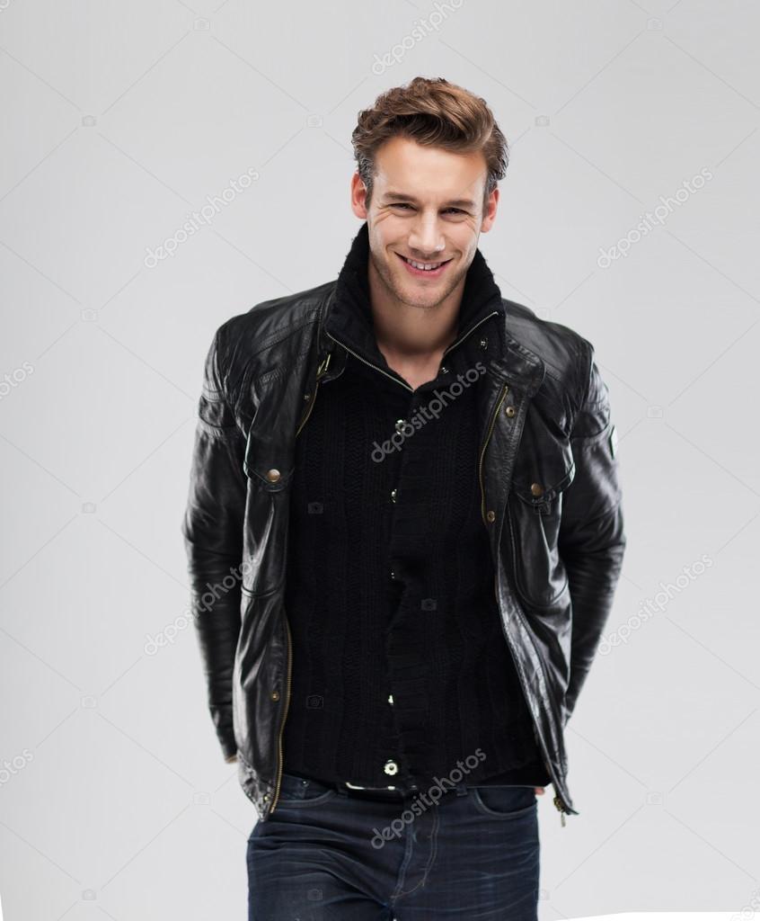 Moda bello sorridente indossa giacca di pelle uomo su sfondo grigio — Foto  di mast3r 1b9e69dd2cc