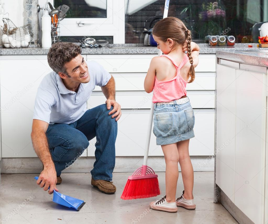 Father and daughter cleaning in the kitchen