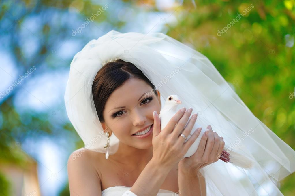 happy attractive bride with white dove un the hands