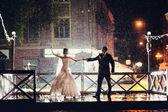Fotografie Braut und Bräutigam tanzen in der Nacht unter Regen