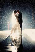 Fotografie Braut und Bräutigam küssen unter Regen in der Nacht