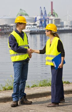Two dockers, a man and a woman shaking hands in an industrial harbor, wearing the necessary safety gear stock vector