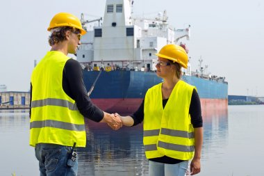Female docker shaking hands with a male coworker in an industrial harbor, in front of a huge freight ship stock vector