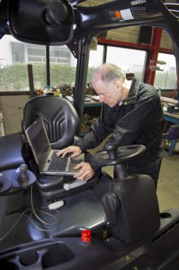 Mechanic checking statistics of forklift