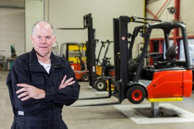 Man in front of forklifts