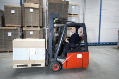 Forklift driving through warehouse