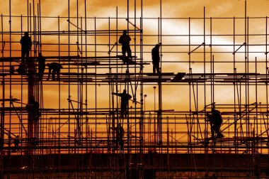 Construction site, silhouettes of workers against the light stock vector