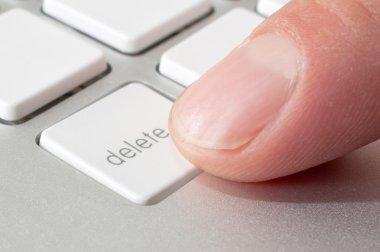 Finger pressing a DELETE key