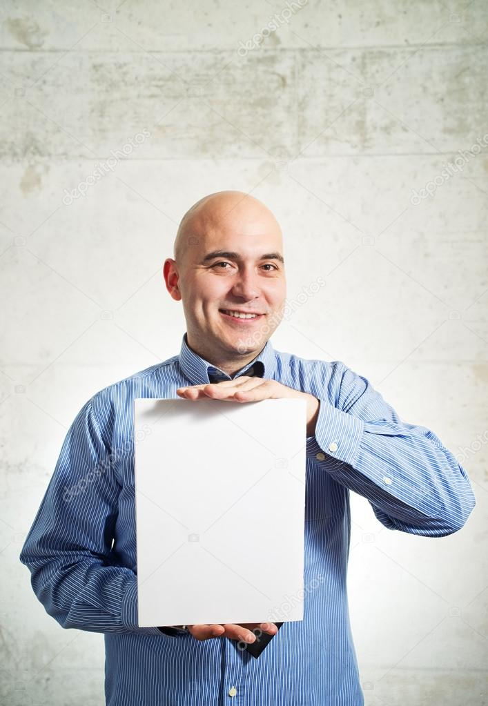 Businessman holding paper. Smiling business man with blank white poster.
