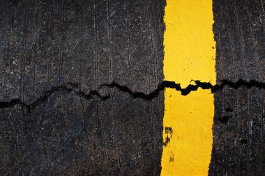 Yellow line on cracked asphalt road