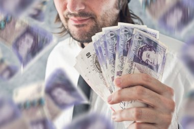 Businessman holding British pounds money, bnknotes falling from