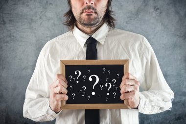 Businessman holding blackboard with question marks