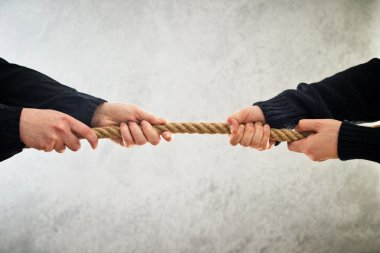 Hands pulling rope to opposite sides