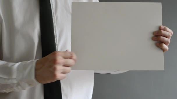 Geschäftsmann hält leeres Papier mit Kopierplatz für geschäftliche Nachrichten