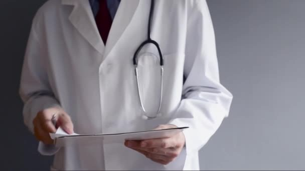 Male doctor is writing RX prescription while standing. Health care professional writing.