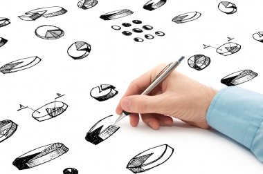 Businessman drawing pie charts and other infographics in note pa