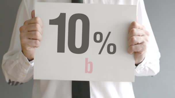Salesman holding sale tag with ten percent sales discount price. Consumerism concept, retail store promotion.