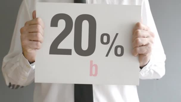 Salesman holding sale tag with twenty percent sales discount price. Consumerism concept, retail store promotion.