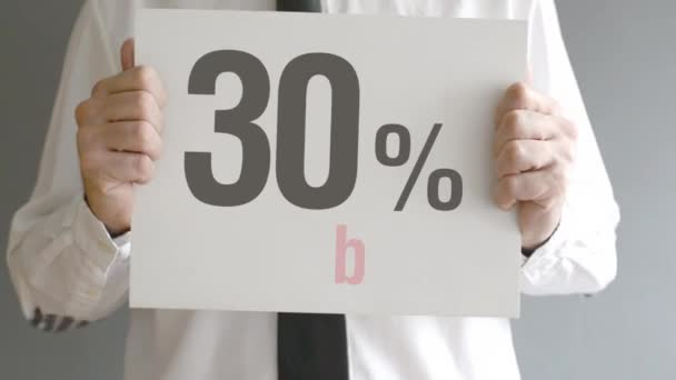 Salesman holding sale tag with thirty percent sales discount price. Consumerism concept, retail store promotion.