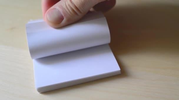 muž obracející stránky malé knihy
