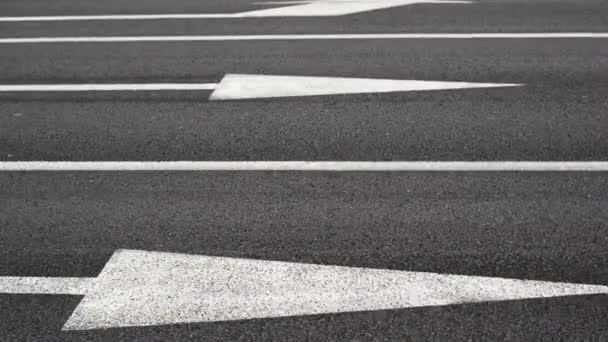 auta křížení silnice. jedno-pásmový provoz. auta v pohybu. zaměřit se na bílé čáry a šipky jako silniční značky a pneumatik automobilů. rušný pouliční život