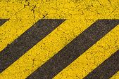 Yellow striped road markings on black asphalt.