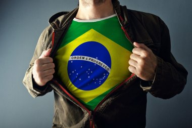 Man stretching jacket to reveal shirt with Brazil flag