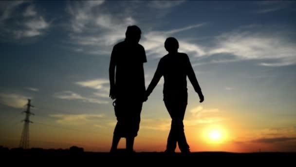 amanti in una data nel tramonto, mano nella mano. scena damore romantico. filmati di 1920 x 1080 full hd.