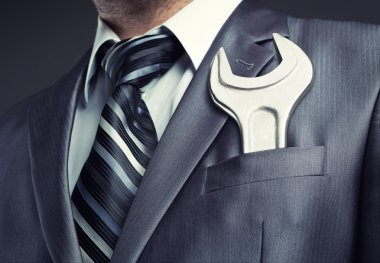 Businessman with spanner in suit pocket stock vector