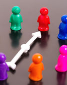 group of toy peoples and white arrow