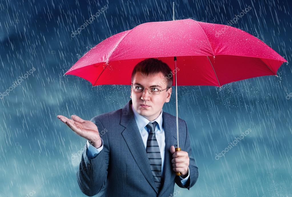 Office worker hiding under an umbrella