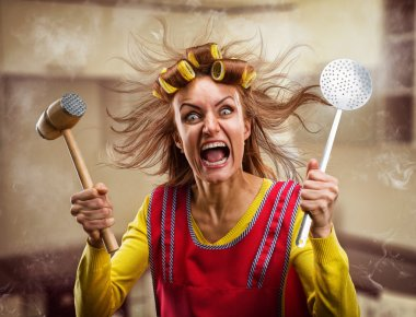 Crazy housewife with kitchen tools