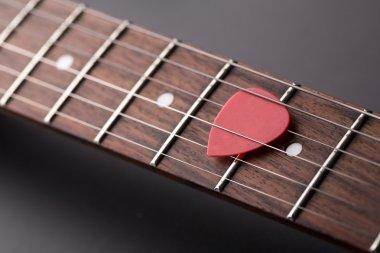 Closeup of red pick in electric guitar strings