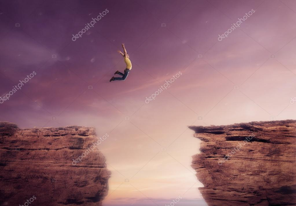 Young man jumping off a cliff